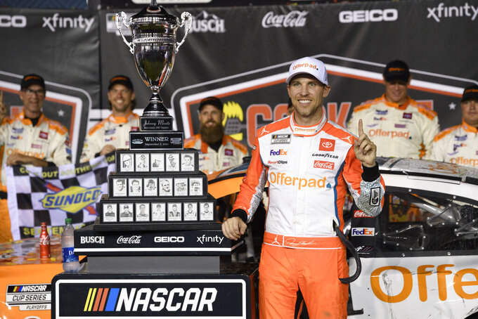 Denny Hamlin stands with the trophy after winning a NASCAR Cup Series auto race Sunday, Sept. 5, 2021, in Darlington, S.C. (AP Photo/John Amis)