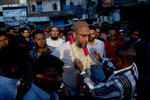 An Indian supporter present a floral garland to All India Majlis-e-Ittehadul Muslimeen (AIMIM) President Asaduddin Owaisi, center, during an election campaign in Hyderabad, India, Tuesday, March 26, 2019. India's national election will be held in seven phases between April 11 and May 19. (AP Photo/ Mahesh Kumar A.)