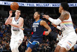 Denver Nuggets center Nikola Jokic, left, flips a pass to guard Gary Harris, right, as Minnesota Timberwolves guard Cameron Reynolds defends during the second half of an NBA basketball game Wednesday, April 10, 2019, in Denver. The Nuggets won 99-95. (AP Photo/David Zalubowski)