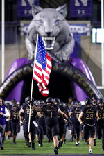 Northwestern defensive lineman Joe Spivak (1) holds a pole bearing a U.S. flag as he runs onto the field with teammates before an NCAA college football game against Michigan State in Evanston, Ill., Friday, Sept. 3, 2021. (AP Photo/Nam Y. Huh)