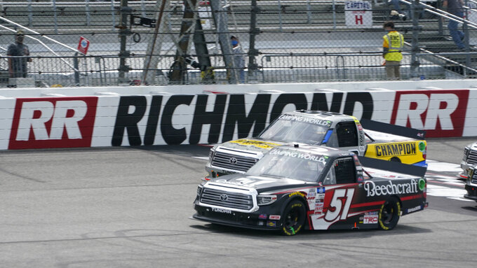 Kyle Busch (51) leads Grant Enfinger (98) during a restart in the NASCAR Truck Series auto race at Richmond International Raceway in Richmond, Va., Saturday, April 17, 2021. (AP Photo/Steve Helber)