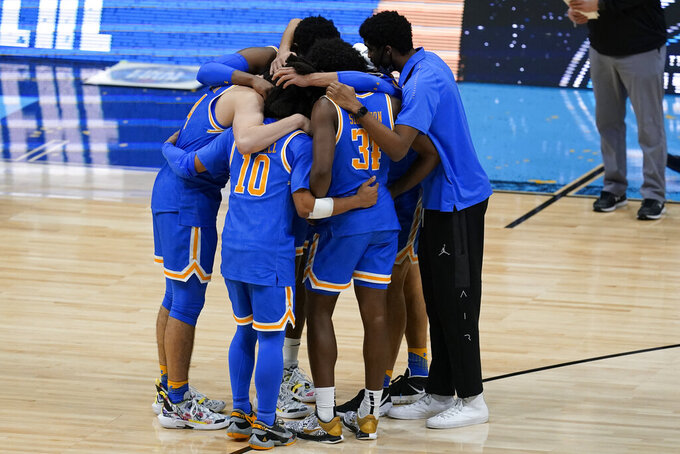 UCLA players huddle on the court after a men's Final Four NCAA college basketball tournament semifinal game against Gonzaga, Saturday, April 3, 2021, at Lucas Oil Stadium in Indianapolis. Gonzaga won 93-90 in overtime. (AP Photo/Darron Cummings)