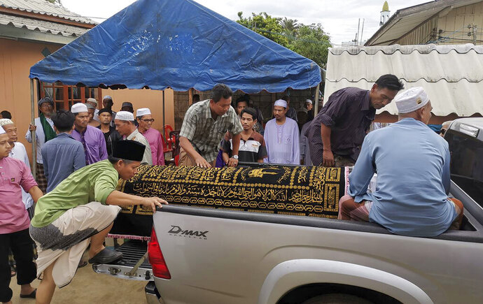 In this Sunday, Aug. 25, 2019, photo, Muslim villagers load the body of Abdulloh Esomuso on the truck to a cemetery in Pattani southern of Thailand. Esomuso was arrested July 20, 2019, on suspicion of being a separatist insurgent and found unconscious the next day in his cell at an army base in the deep south province of Pattani. He died on Sunday, Aug. 25, with his family and human rights groups seeking an investigation of whether his death was due to torture. (AP Photo)