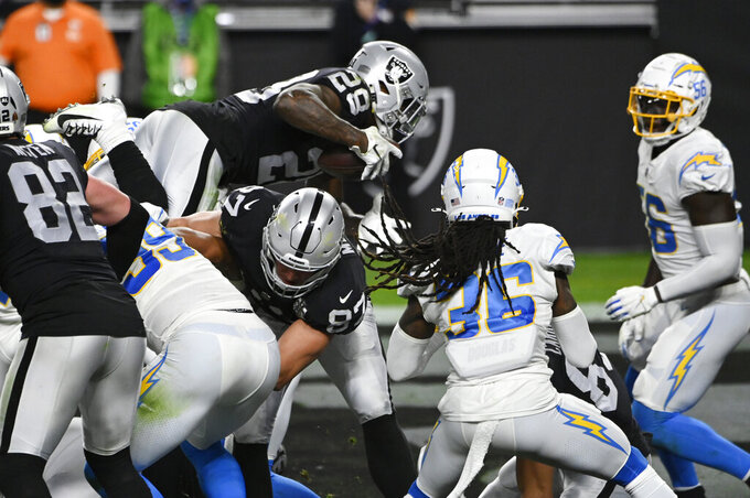 Las Vegas Raiders running back Josh Jacobs (28) dives into the end zone for a touchdown against the Los Angeles Chargers during the second half of an NFL football game, Thursday, Dec. 17, 2020, in Las Vegas. (AP Photo/David Becker)