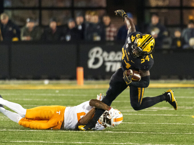Missouri running back Larry Rountree III, right, is tripped up by Tennessee defensive back Alontae Taylor during the fourth quarter of an NCAA college football game, Saturday, Nov. 23, 2019, in Columbia, Mo. Tennessee won the game 24-20. (AP Photo/L.G. Patterson)