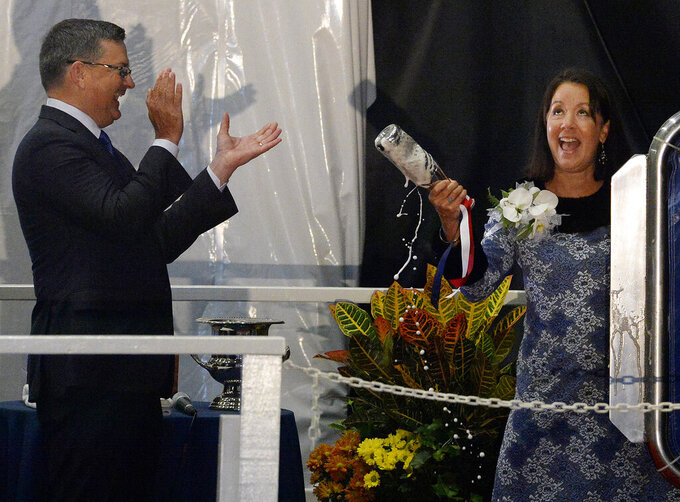 FILE - In this Oct. 5, 2019 file photo, Kevin Graney, president of General Dynamics Electric Boat applauds as Dana Richardson breaks a champaign bottle on the second try during the christening ceremony for the U.S. Navy's newest attack submarine at Electric Boat shipyard in Groton, Conn. On Saturday, April 4, 2020, Graney told Electric Boat employees that he has tested positive for the new coronavirus. Graney got the results of his test the night before. (Dana Jensen/The Day via AP, File)