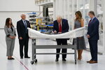 President Donald Trump signs a piece of equipment as he and first lady Melania Trump participate in a tour of NASA facilities before viewing the SpaceX Demonstration Mission 2 Launch at Kennedy Space Center, Wednesday, May 27, 2020, in Cape Canaveral, Fla. Vice President Mike Pence, second from left, second lady Karen Pence, left, and NASA Administrator Jim Bridenstine look on. (AP Photo/Evan Vucci)