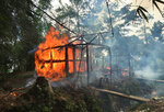 FILE - In this Sept. 7, 2017, file photo, houses are on fire in Gawdu Zara village, northern Rakhine state, Myanmar. Two soldiers who defected from Myanmar's army and confessed on video to taking part in massacres, rape, and other crimes against the Muslim Rohingya minority are believed to be in the custody of the International Criminal Court in the Netherlands and should be prosecuted to obtain their evidence, a human rights organization said Tuesday. (AP Photo, File)
