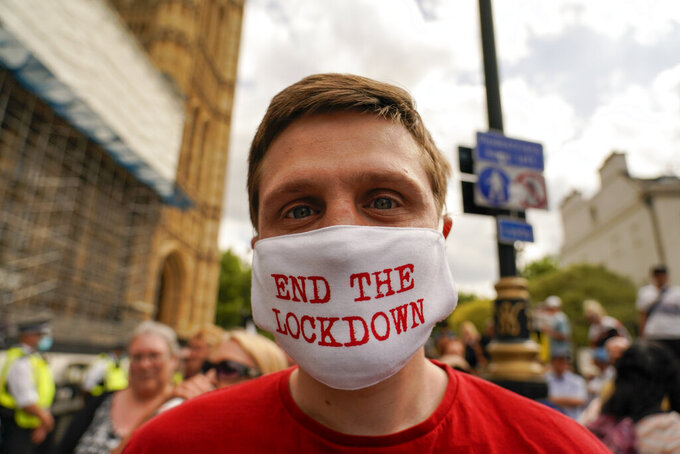 A man wears a mask reading 'End the lockdown' outside the Palace of Westminster, to protest against the delay of the planned relaxation of lockdown measures, in London, Monday, June 14, 2021. British Prime Minister Boris Johnson is expected to confirm Monday that the next planned relaxation of coronavirus restrictions in England will be delayed as a result of the spread of the delta variant first identified in India. (AP Photo/Alberto Pezzali)