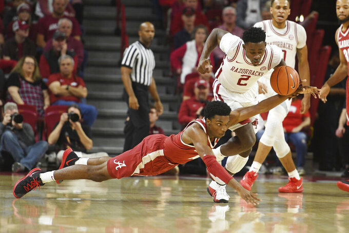 Arkansas forward Adrio Bailey (2) and Alabama guard Herbert Jones (10) go after the ball during the first half of an NCAA college basketball game, Saturday, March 9, 2019 in Fayetteville, Ark. (AP Photo/Michael Woods)