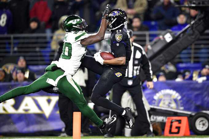 Baltimore Ravens wide receiver Seth Roberts, right, makes a touchdown catch on a pass from quarterback Lamar Jackson,not visible, as New York Jets free safety Marcus Maye (20) defends during the second half of an NFL football game, Thursday, Dec. 12, 2019, in Baltimore. (AP Photo/Nick Wass)