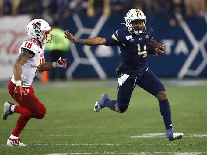 Georgia Tech quarterback James Graham (4) runs away from North Carolina State safety Tanner Ingle (10) during the second half of an NCAA college football game Thursday, Nov. 21, 2019, in Atlanta. Georgia Tech won 28-26. (AP Photo/John Bazemore)