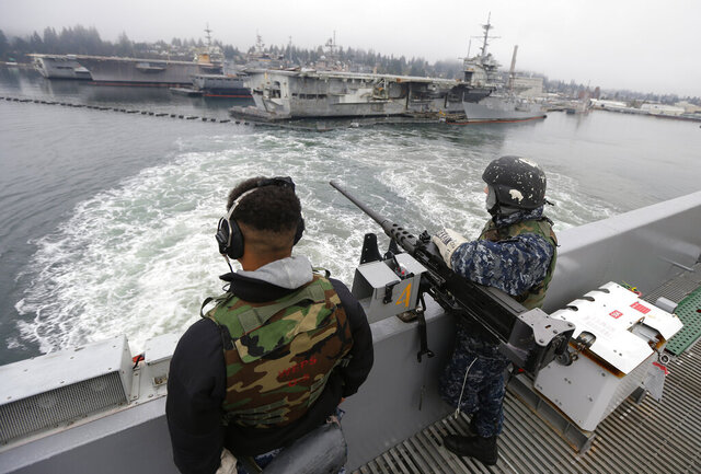 FILE - In this Jan. 13, 2015, file photo, two sailors stand with a gun as the USS John Stennis aircraft carrier leaves Naval Base Kitsap in Washington state. A federal judge in Seattle ruled Thursday, Feb. 27, 2020, that President Donald Trump cannot divert $89 million intended for a construction project at the base to help build his wall on the U.S.-Mexico border. (AP Photo/Ted S. Warren, File)