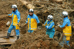 Police officers carry earth and sand by buckets as they search for the missing in Tsunagi town, Kumamoto prefecture, southern Japan Friday, July 10, 2020. Parts of Japan still searching for missing people and trying to repair damages from deadly floods and mudslides were bracing for more pounding rains through the weekend. (Kyodo News via AP)