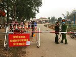 Police wearing masks guard a road checkpoint before entering the Son Loi commune in Vinh Phuc province, Vietnam, on Thursday, Feb. 13, 2020. 0fficial media reported that the Son Loi commune with 10,000 residents northwest of the capital Hanoi was put in lockdown due to a cluster of cases of the COVID-19 disease there. Vietnam has confirmed 16 cases of the disease. (AP Photo/Yves Dam Van)