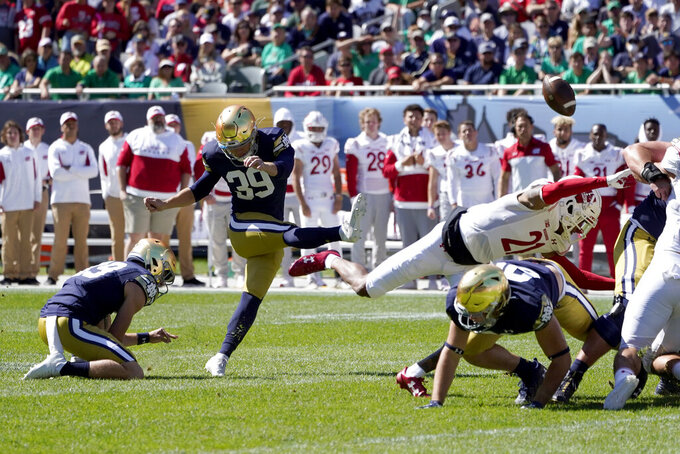 Notre Dame place kicker Jonathan Doerer kicks a field goal off the hold of Jay Bramblett during the first half of an NCAA college football game against Wisconsin Saturday, Sept. 25, 2021, in Chicago. (AP Photo/Charles Rex Arbogast)