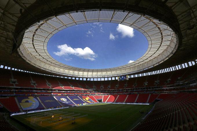Employees prepare the National Stadium for the tomorrow's Copa America soccer tournament in Brasilia, Brazil, Saturday, June 12, 2021. The stadium will host Sunday's opening match between Brazil and Venezuela. (AP Photo/Eraldo Peres)