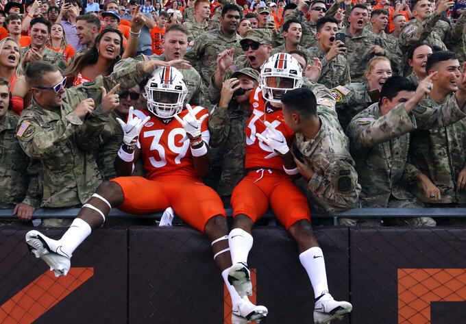 Virginia Tech's Ty Eller (39) and Jalen Hampton (36) pose with members of the Virginia Tech Corps of Cadets at the start of the team's NCAA college football game against North Carolina on Friday, Sept. 3, 2021, in Blacksburg, Va. (Matt Gentry/The Roanoke Times via AP)