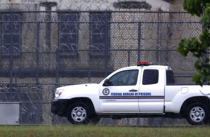 A Federal Bureau of Federal Prisons truck drives past barbed wire fences at the Federal Medical Center prison in Fort Worth, Texas, Saturday, May 16, 2020. Hundreds of inmates inside the facility have tested positive for COVID-19 and several inmates have died with numbers expected to rise. (AP Photo/LM Otero)