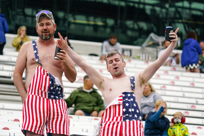 Fans yell from the stands as rain delayed the start of the final practice session for the Indianapolis 500 auto race at Indianapolis Motor Speedway in Indianapolis, Friday, May 28, 2021. (AP Photo/Michael Conroy)