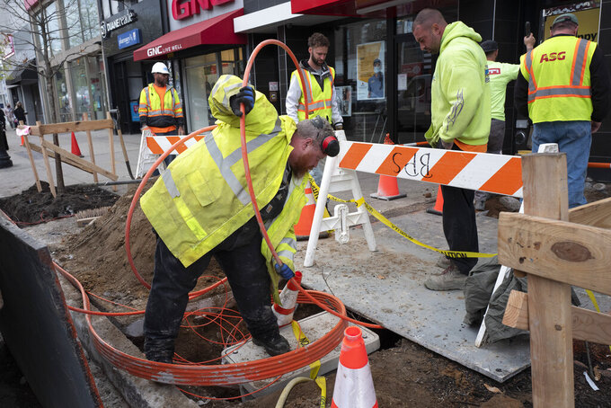 FILE - In this April 21, 2021 file photo, workers install conduit that will hold Verizon's fiber-optic cable in New York.   U.S. productivity posted a sharp rebound in the January-March quarter after having fallen in the previous quarter. Labor costs declined slightly.  (AP Photo/Mark Lennihan)