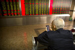 A Chinese investor uses his smartphone as he monitors stock prices at a brokerage house in Beijing, Wednesday, March 20, 2019. Markets in Asia are mostly lower after a lackluster day of trading on Wall Street.(AP Photo/Mark Schiefelbein)