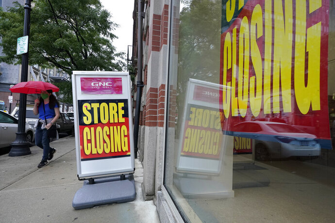 FILE - In this Sept. 2, 2020, file photo, a passerby walks past a business storefront with store closing signs in Boston. The U.S. unemployment rate dropped to 7.9% in September, but hiring is slowing and many Americans have given up looking for work, the government said Friday, Oct. 2, in the final jobs report before the voters decide whether to give President Donald Trump another term. (AP Photo/Steven Senne, File)