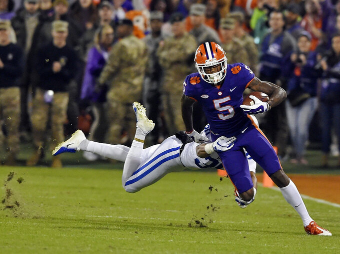 Clemson's Tee Higgins runs with a pass reception while defended by Duke's Brandon Feamster during the first half of an NCAA college football game Saturday, Nov. 17, 2018, in Clemson, S.C. (AP Photo/Richard Shiro)