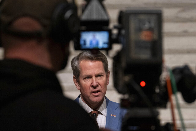 Georgia Gov. Brian Kemp, center, holds a press conference Wednesday evening, Jan. 6, 2021, at the Georgia State Capitol in Atlanta, to condemn the breach of the U.S. Capitol. (AP Photo/Ben Gray)