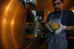 Chef Jesus Saldivar removes freshly made tortillas from the tortilla making machine at El Pujol Mill in the Condesa neighborhood of Mexico City, Tuesday, April 9, 2019. The shop is part of a new tortilla movement launched by a handful of chefs, restaurants and organizations to restore and popularize authentic tortillas, made of only corn, water and lime or calcium carbonate. (AP Photo/Rebecca Blackwell)