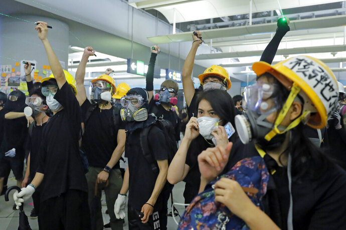 Demonstrators shine laser pointers during a protest at the Yuen Long MTR station in Hong Kong, Wednesday, Aug. 21, 2019. Hong Kong riot police faced off briefly with protesters occupying a suburban train station Wednesday evening following a commemoration of a violent attack there by masked assailants on supporters of the anti-government movement. (AP Photo/Kin Cheung)