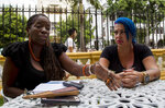 In this June 28, 2019, photo, Dianelys Alfonso, right, singer, sits with her lawyer Deyni Terry, for a photo during an interview with The Associated Press in Havana, Cuba. Alfonso publicly denounced another renowned musician, flutist and bandleader José Luis Cortés, accusing him of repeatedly hitting and raping her during her time as vocalist for NG La Banda. Terry said she and her client are still investigating whether they can bring charges of abuse and sexual assault against Cortés many years after the alleged crimes took place. (AP Photo/Ismael Francisco)