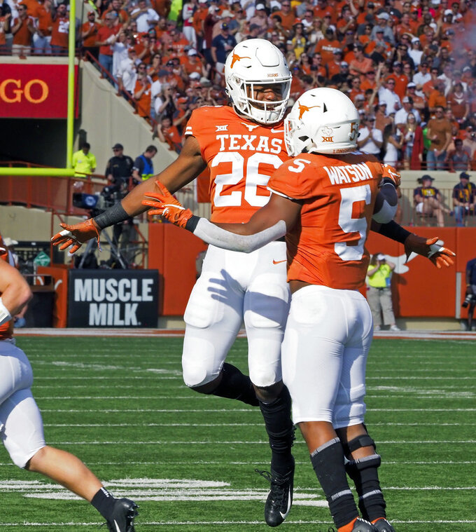 Texas' Tre Watson (5) celebrates his touchdown run with Texas' Keaontay Ingram (26) during the first half of an NCAA college football game against West Virginia, Saturday, Nov. 3, 2018, in Austin, Texas. (AP Photo/Michael Thomas)