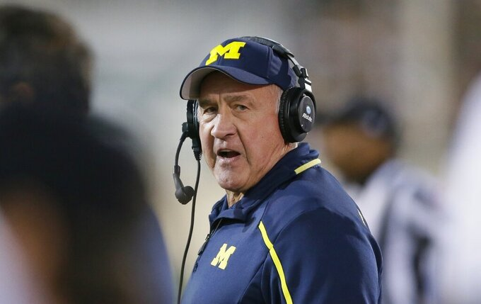 FILE - In this Saturday, Oct. 25, 2014 file photo, Michigan defensive coordinator Greg Mattison walks the sidelines during the second half of an NCAA college football game against Michigan State in East Lansing, Mich. New Buckeyes coach Ryan Day swiped Mattison from Michigan. One of the most respected defensive coaches in the country, the 69-year-old Mattison now joins forces with the 40-year-old Hafley to remake a defense that was maybe the worst in school history last year. Scheme tweaks include the use of a promising defensive back Shaun Wade in a safety/linebacker hybrid role.  (AP Photo/Carlos Osorio, File)