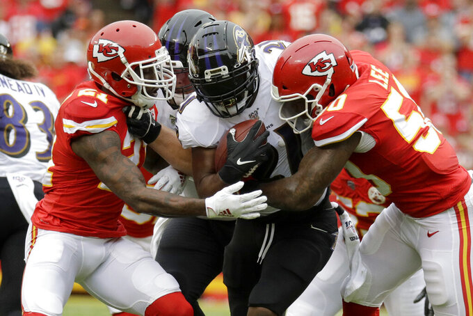 Baltimore Ravens running back Mark Ingram II, center, carries the ball between Kansas City Chiefs cornerback Bashaud Breeland (21) and linebacker Darron Lee (50) during the first half of an NFL football game in Kansas City, Mo., Sunday, Sept. 22, 2019. (AP Photo/Charlie Riedel)
