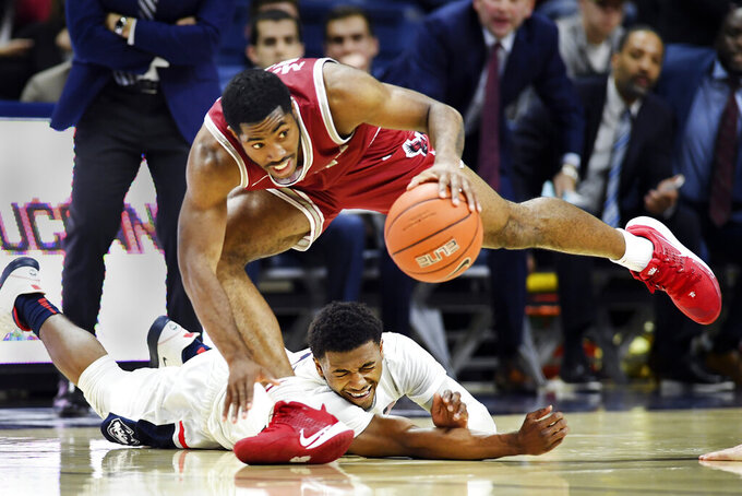 Connecticut's Alterique Gilbert (3) and Saint Joseph's guard Rahmir Moore (10) battle for possession late in the second half of an NCAA college basketball game Wednesday, Nov. 13, 2019, in Storrs, Conn. (AP Photo/Stephen Dunn)