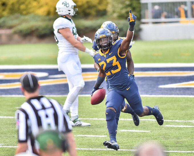 FILE - West Virginia's Tykee Smith (23) reacts after making an interception in overtime against Baylor during an NCAA college football game in Morgantown, W.V., in this Saturday, Oct. 3, 2020, file photo. Tykee Smith transferred to Georgia. Tykee Smith had 61 tackles – eight for loss – and two interceptions in 10 games for West Virginia last season. (William Wotring/The Dominion-Post via AP)