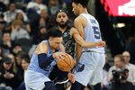 Memphis Grizzlies guard Dillon Brooks (24) tries to work the ball around San Antonio Spurs guard Patty Mills, center, during the second half of an NBA basketball game, in San Antonio, Monday, Nov. 11, 2019. (AP Photo/Eric Gay)