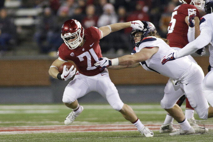 "FILE - In this Nov. 17, 2018, file photo, Washington State running back Max Borghi (21) runs while under pressure from Arizona linebacker Colin Schooler during the first half of an NCAA college football game in Pullman, Wash. The departure of James ""Boobie"" Williams should mean more exposure for Borghi, who earned a starting job last year as a freshman and is expected to be the primary option in the backfield. (AP Photo/Young Kwak, File)"