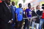 FILE - In this Aug. 13, 2019 file photo, Delisha Searcy, mother of De'Von Bailey, at podium, speaks at a news conference in front of the Colorado Springs Police Department Police Operations Center in Colorado Springs, Colo. Greg Bailey, third from left, De'Von Bailey's father, stands next to Searcy. Police body camera video released Thursday, Aug. 15, 2019 shows De'Von Bailey being shot by police while running away. (Jerilee Bennett/The Gazette via AP, File)