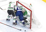 Dallas Stars goaltender Anton Khudobin (35) makes a save as Tampa Bay Lightning center Brayden Point (21) and Stars defenseman Miro Heiskanen (4) crash into the net during the first overtime in Game 5 of the NHL hockey Stanley Cup Final, Saturday, Sept. 26, 2020, in Edmonton, Alberta. (Jason Franson/The Canadian Press via AP)