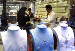 Saudis buy jewels at the gold market a day before the expected increase of VAT from 5% to15%, in Jiddah, Saudi Arabia, Tuesday, June 30, 2020. (AP Photo/Amr Nabil)
