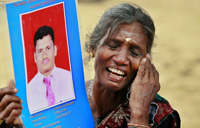 In this Friday, Nov. 15, 2013, file photo, a Sri Lankan ethnic Tamil woman cries holding a portrait of her missing son during a protest in Jaffna, Sri Lanka. Sri Lanka's president has decided that tens of thousands of people still missing from the country's quarter-century civil war will be formally declared dead and death certificates will be issued, his office said Monday. (AP Photo/Eranga Jayawardena)