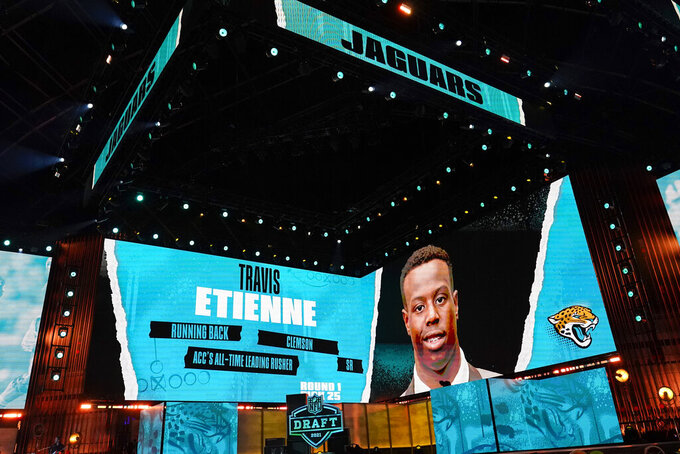 An image of Clemson running back Travis Etienne is displayed on stage after he was chosen by the Jacksonville Jaguars with the 25th pick in the first round of the NFL football draft Thursday April 29, 2021, in Cleveland. (AP Photo/Tony Dejak)