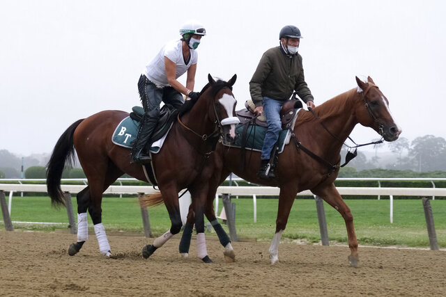 Belmont Stakes hopeful Robin Smullen on Tiz the Law, left, is led around the track by trainer Barclay Tagg during a workout at Belmont Park in Elmont, N.Y., Friday, June 19, 2020. (AP Photo/Seth Wenig)