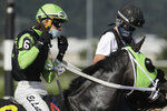 Jockey Francisco Diaz-Lopez, left, adjusts his face mask Wednesday, June 24, 2020, before a race at Emerald Downs Racetrack in Auburn, Wash., on the first day of thoroughbred horse racing at the track since all professional sports in Washington state were curtailed in March by the outbreak of the coronavirus. No spectators were allowed, but online wagering was available and the races were streamed. Organizers hope to continue racing into October on a modified schedule. (AP Photo/Ted S. Warren)
