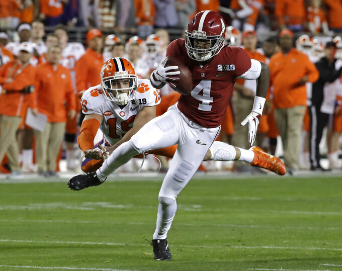 FILE - In this Jan. 7, 2019, file photo, Alabama's Jerry Jeudy catches a touchdown pass in front of Clemson's Tanner Muse during the first half the NCAA college football playoff championship game in Santa Clara, Calif. College football's race for its top individual awards this season will have a couple of standout players seeking repeats. Wisconsin's Jonathan Taylor won the Doak Walker Award as the nation's top running back last season, while Alabama's Jerry Jeudy earned the Fred Biletnikoff Award as college football's most outstanding receiver. Both players are back for their junior seasons. (AP Photo/Chris Carlson, File)