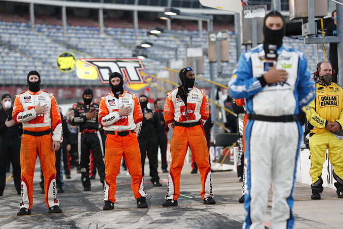 Crew members stand during the national anthem before a NASCAR Truck Series auto race at Charlotte Motor Speedway Tuesday, May 26, 2020 in Concord, N.C. (AP Photo/Gerry Broome)