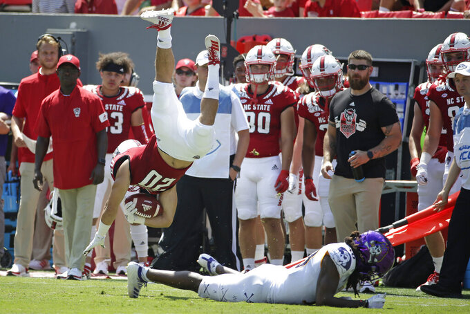 North Carolina State running back Jordan Houston (20) dives over East Carolina linebacker Chad Stephens (40) during the first half of an NCAA college football game in Raleigh, N.C., Saturday, Aug. 31, 2019. (AP Photo/Gerry Broome)
