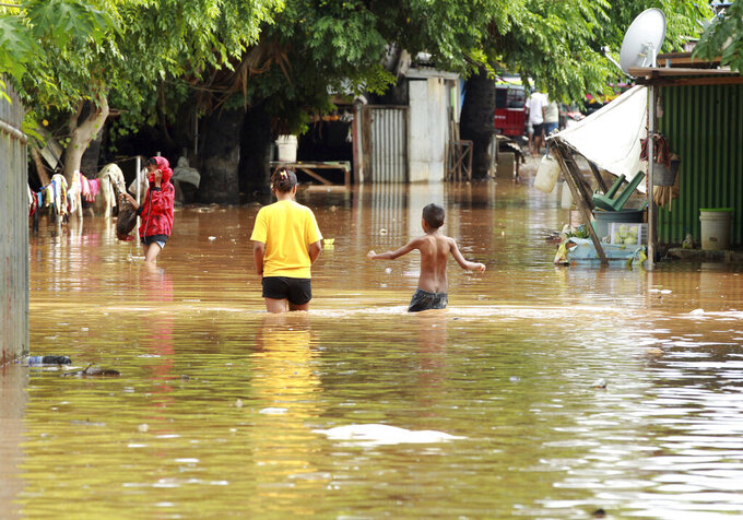 People wade through flood waters in Dili, East Timor, Monday, April 5, 2021. Multiple disasters caused by torrential rains in eastern Indonesia and neighboring East Timor have left dozens of people dead and missing and displaced thousands. (AP Photo/Kandhi Barnez)